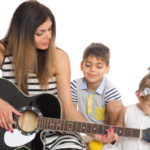 Eine Mutter spielt Gitarre für ihre Kinder