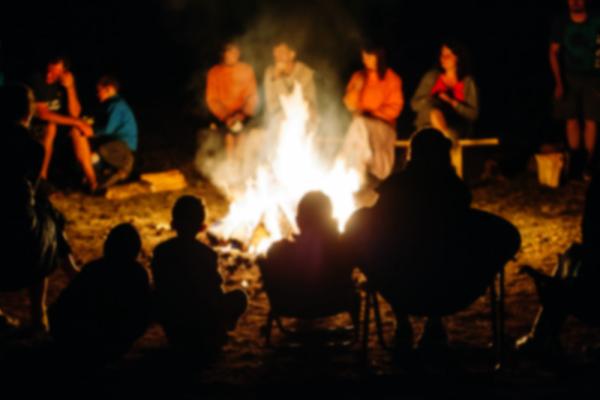 Freunde sitzen um ein Lagerfeuer mit Gitarre